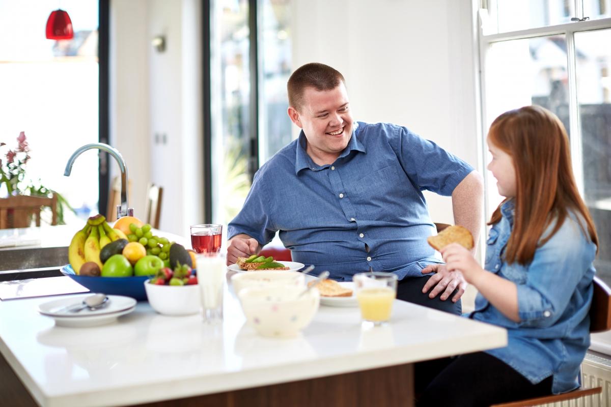 Dad & daughter in kitchen eating