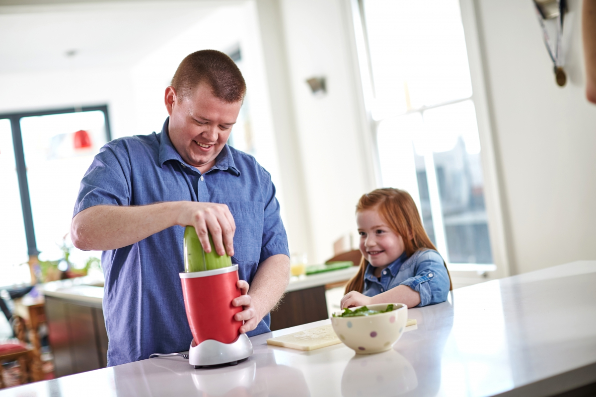 Dad making healthy smoothie for daughter