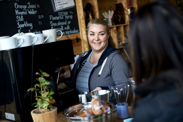 Woman in a coffee shop taking an order