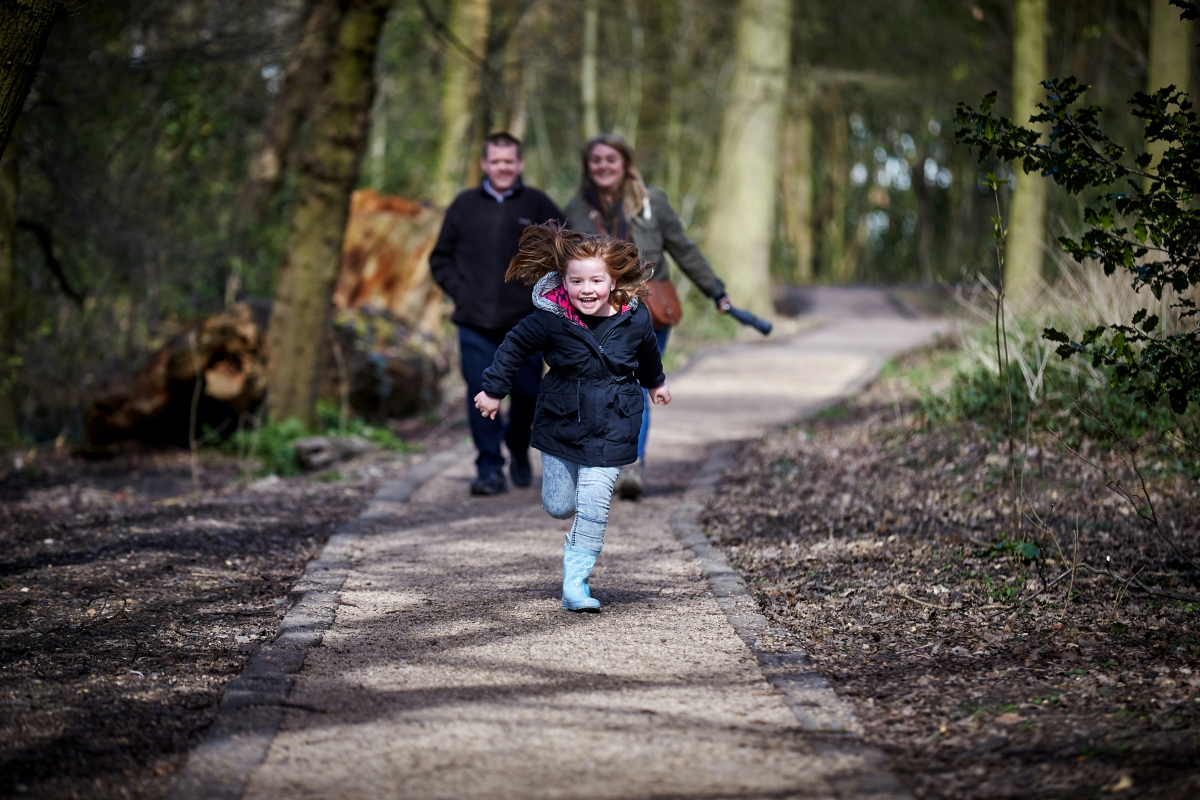 Girl running in woods as parents watch