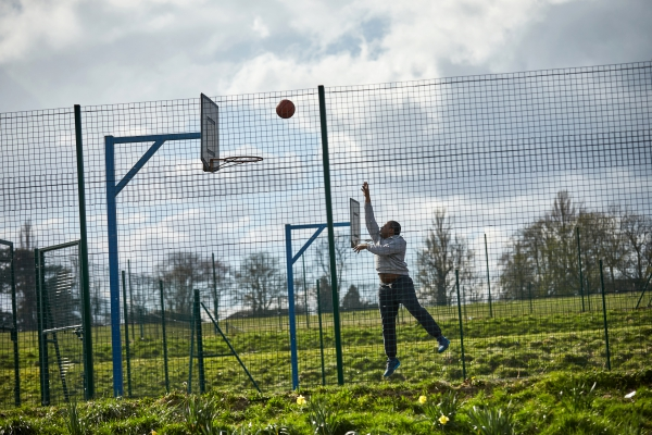 Man shooting hoops on basketball court