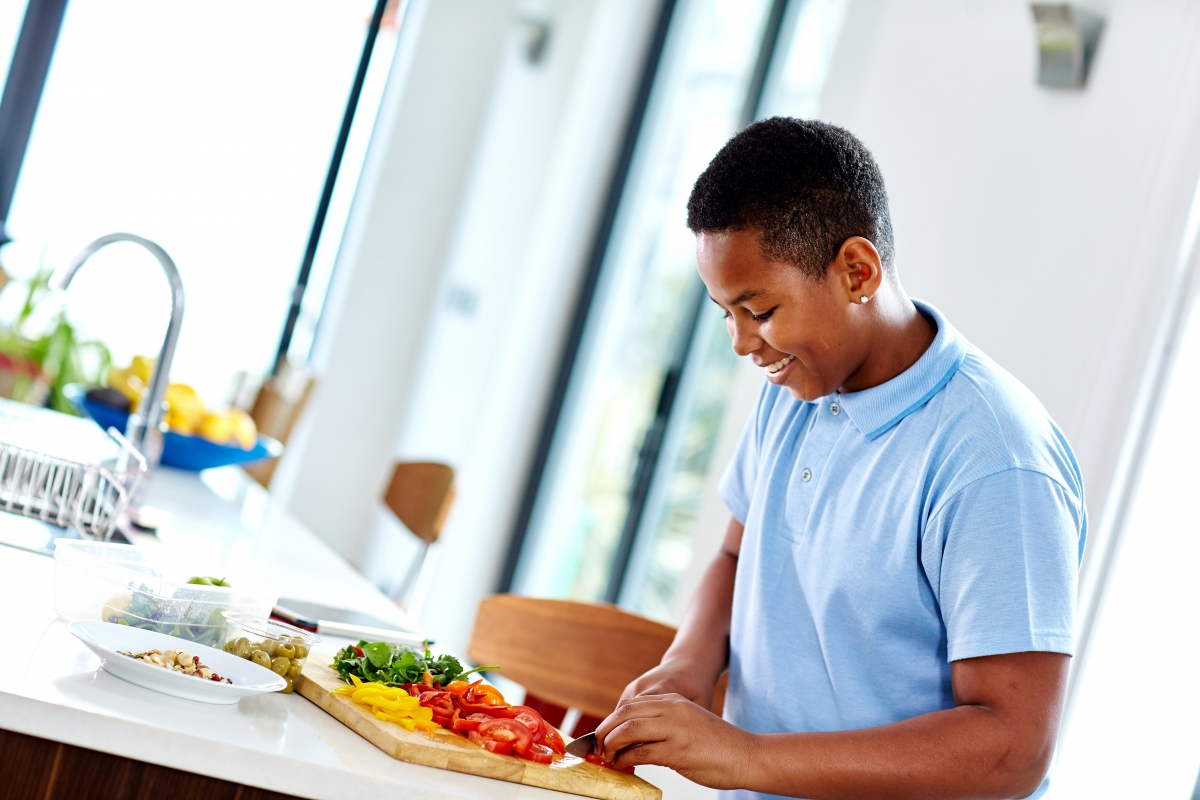 Boy chopping vegetables in Kitchen
