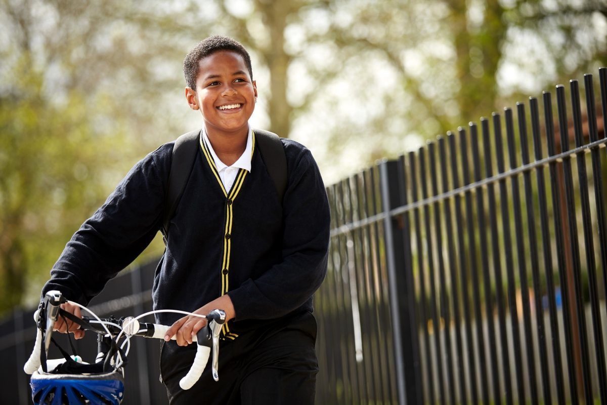 Boy pushing his bike on way to school