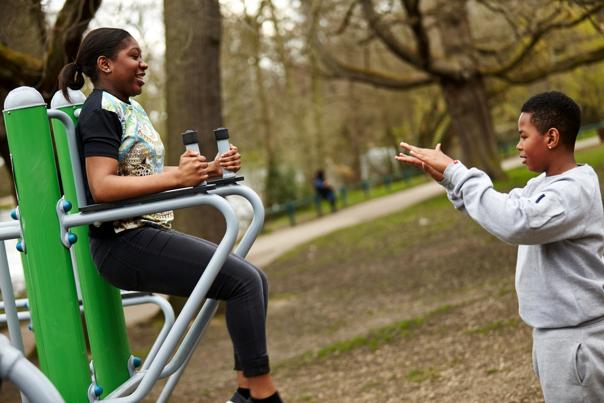 Teenagers on exercise equipment in park