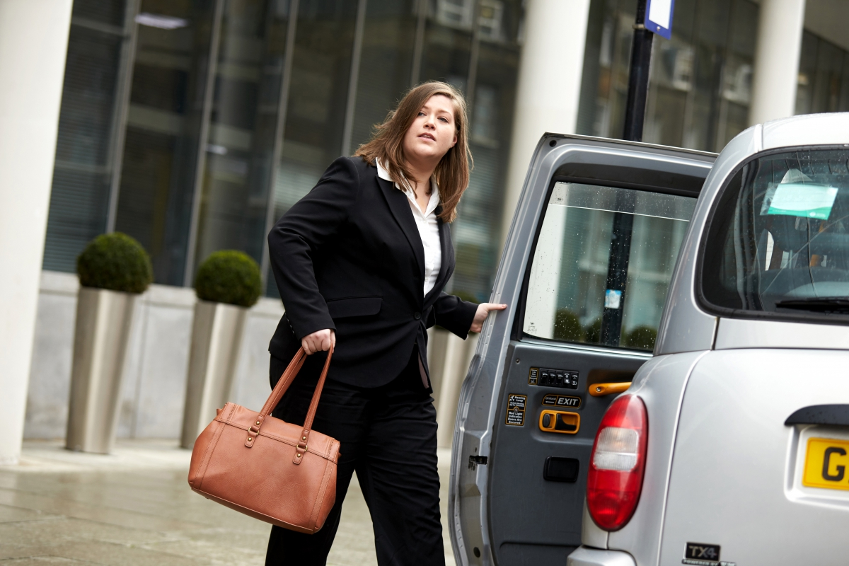 Business woman getting into a taxi