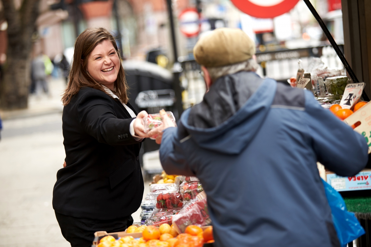 Man handing fruit to business woman