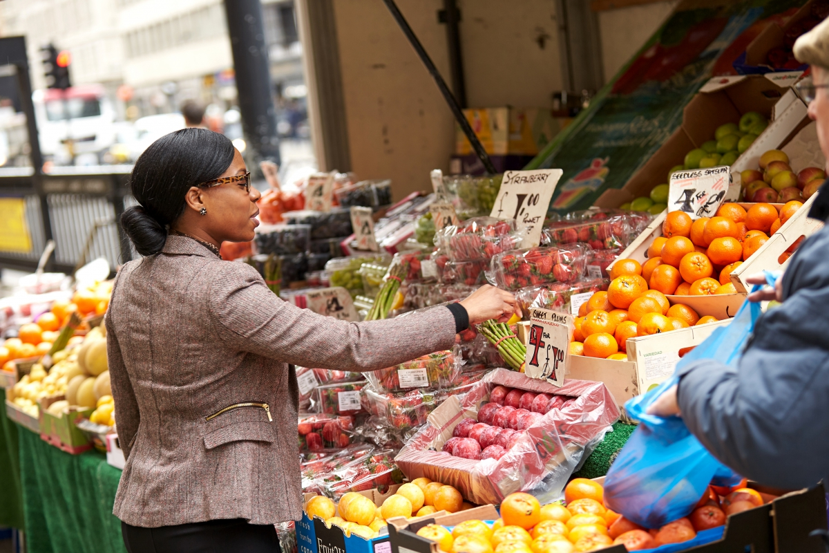 Business woman checking fruit on a stall