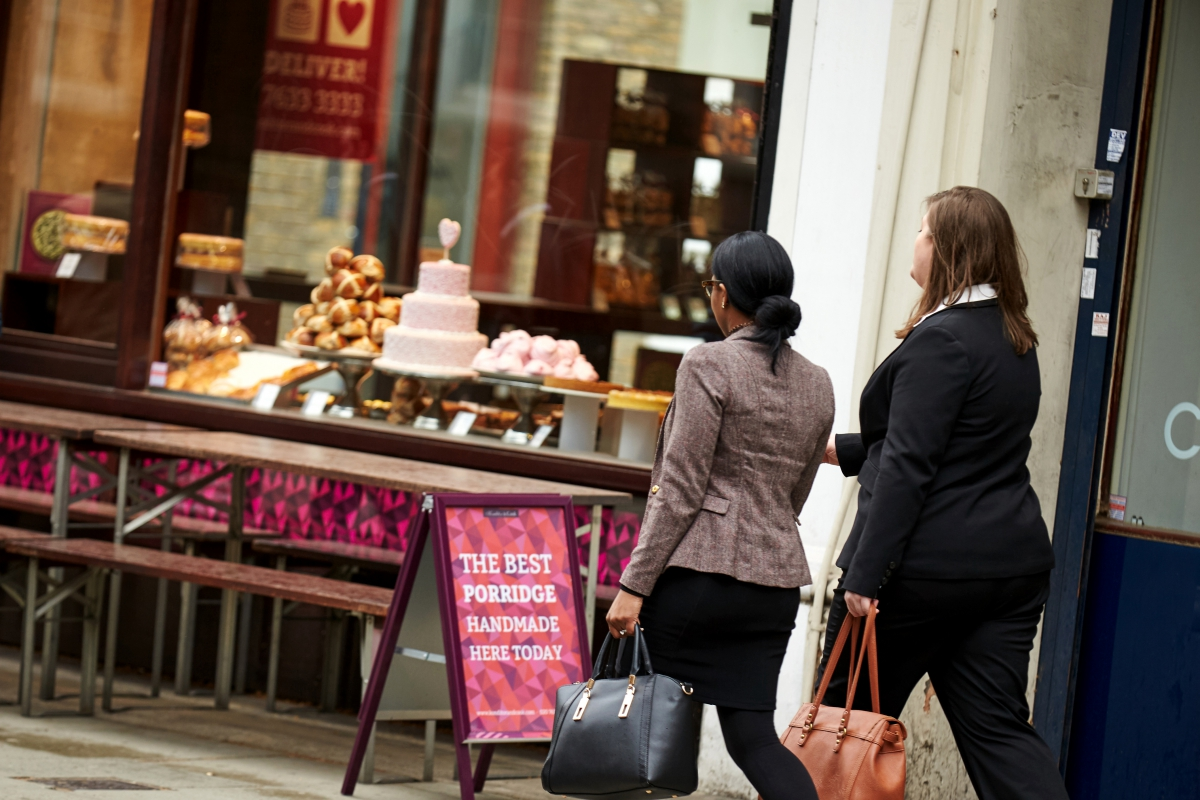 Two business women walking past a bakery