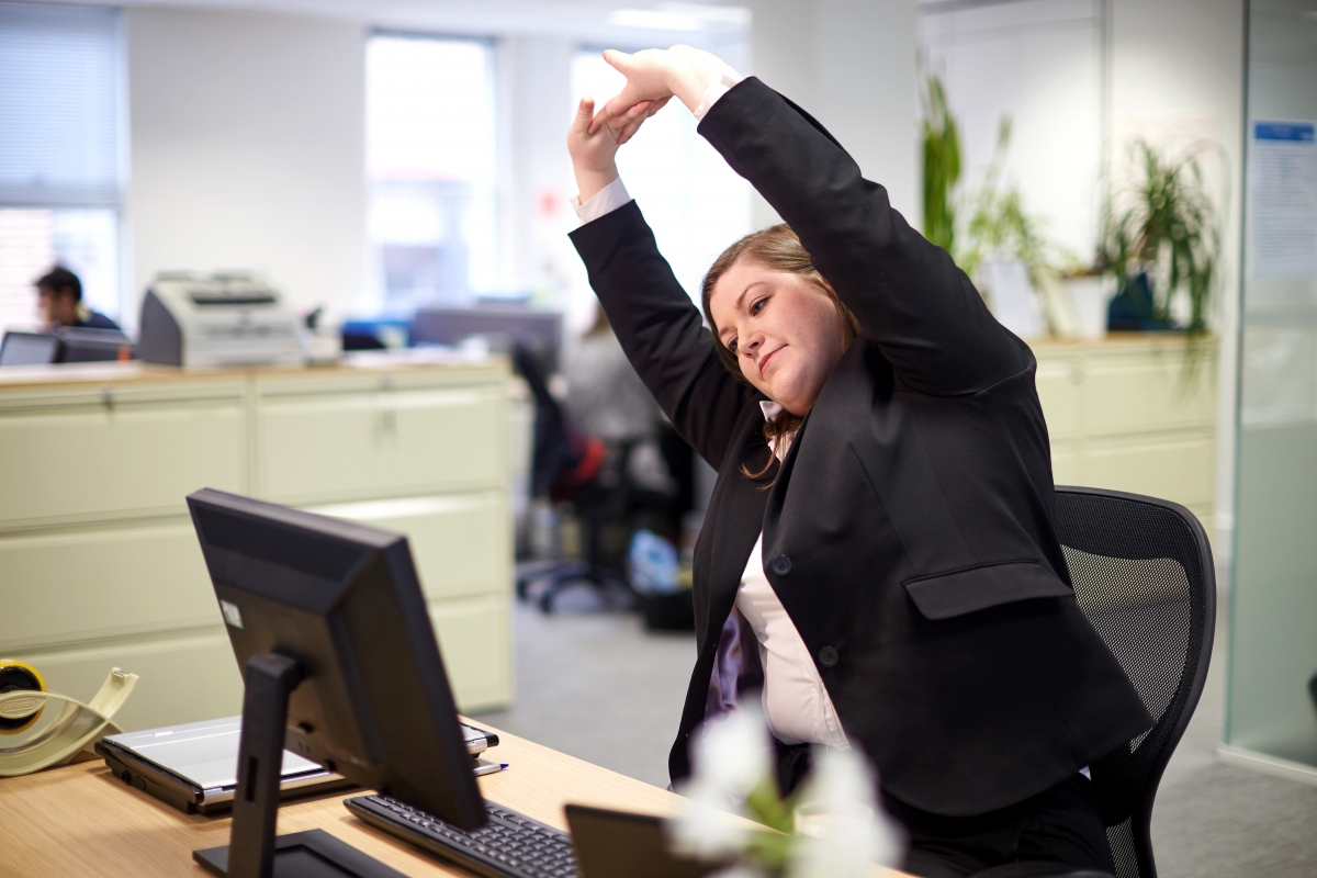 Employee stretching at desk